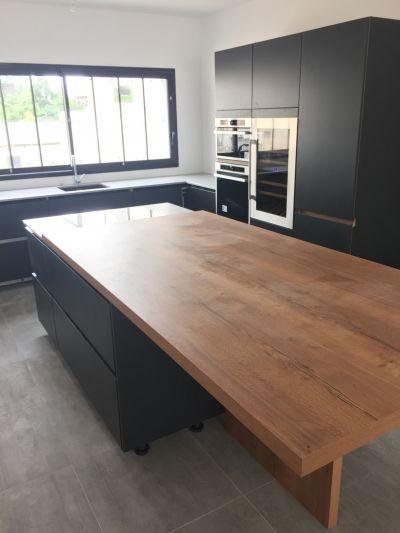 La cuisine, avec son plan de travail Dekton autour de l'evier et de la plaque de cuisson et la table en bois de 2,4m