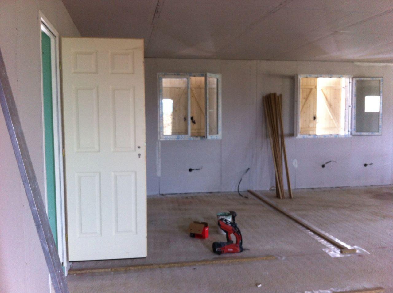 La porte qui mènera au garage avec en arrière plan deux futures chambres.