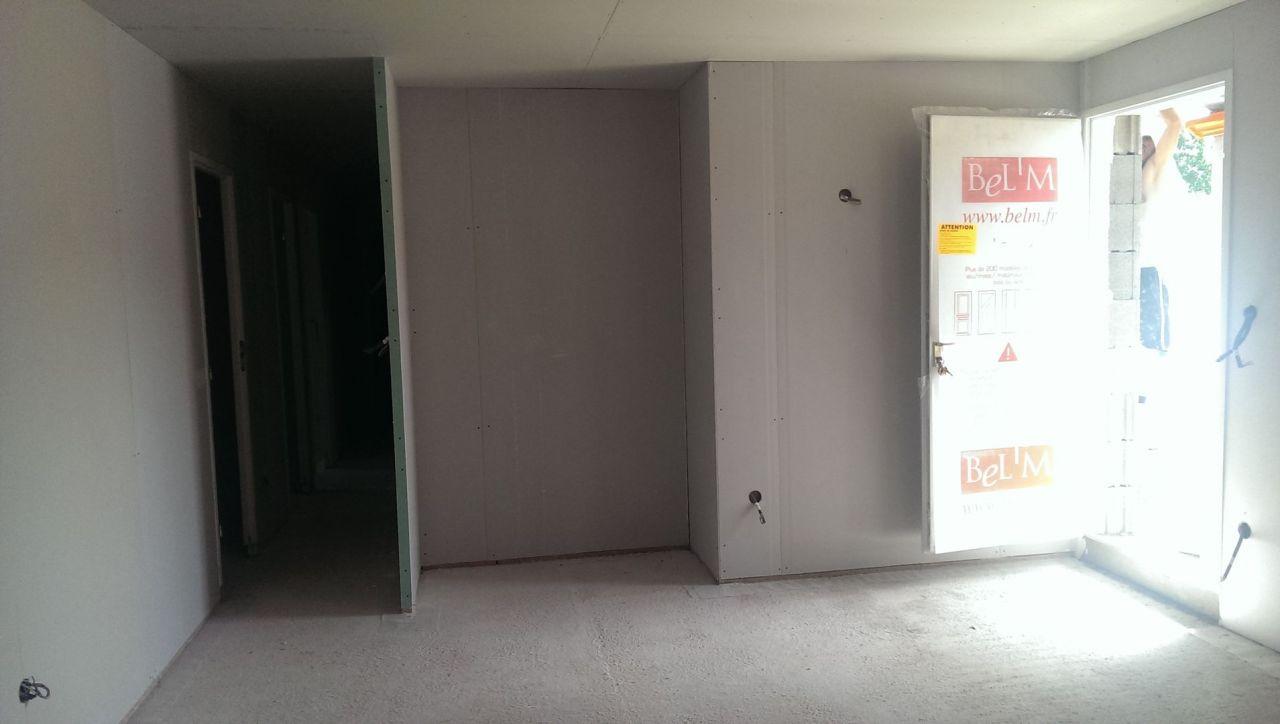 L'entrée et à gauche le couloir menant aux chambres et pièces d'eau.