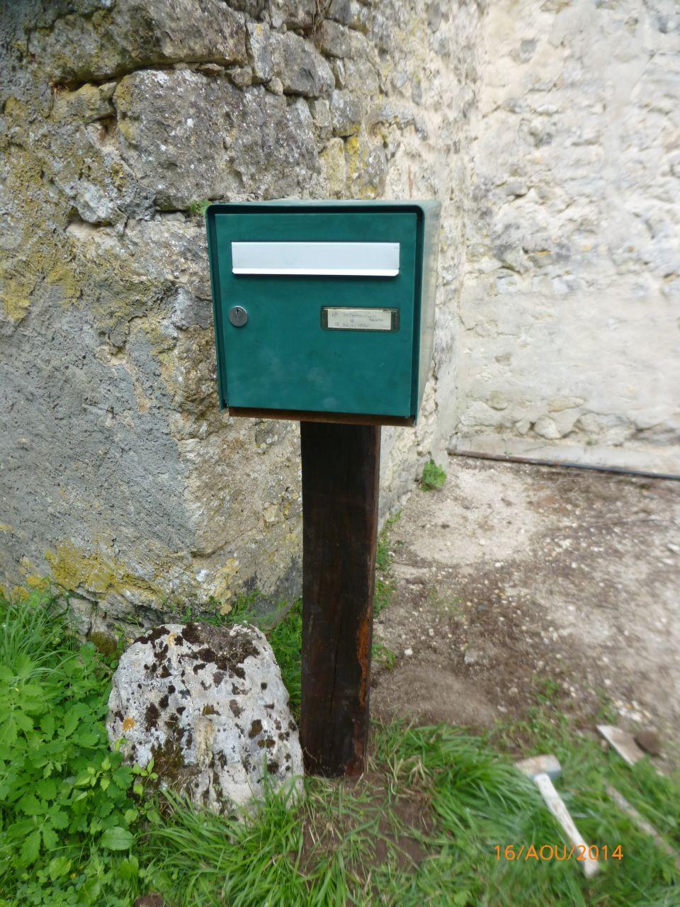 un poil d'imagination/bricolage, une boite d'occasion, une vieille poutre et un gros caillou, nous voila avec une vrai boite au lettre