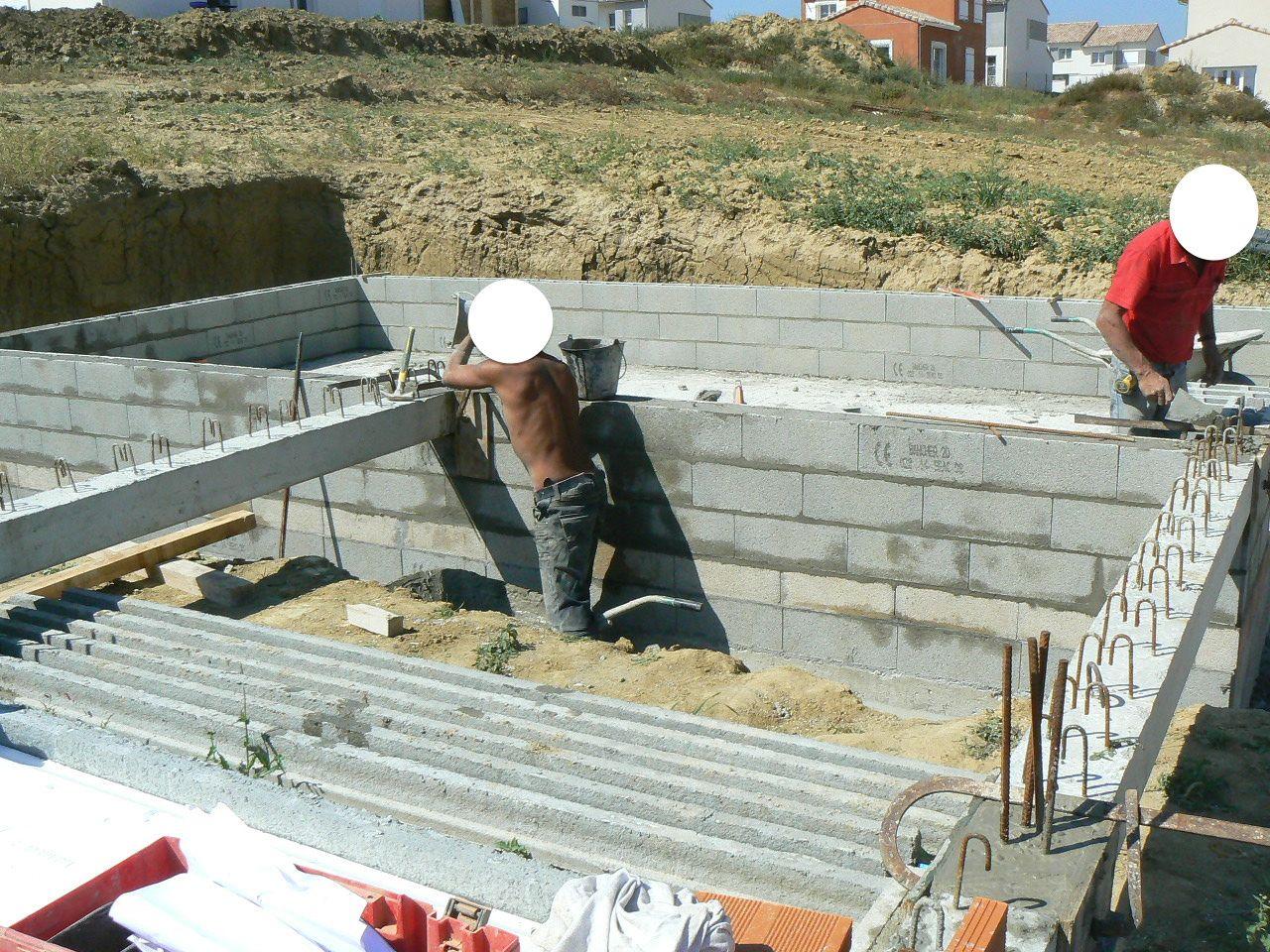 Mise en place des poutres du plancher du rez de chaussée repris par le mur de blocs à BANCHER du garage.