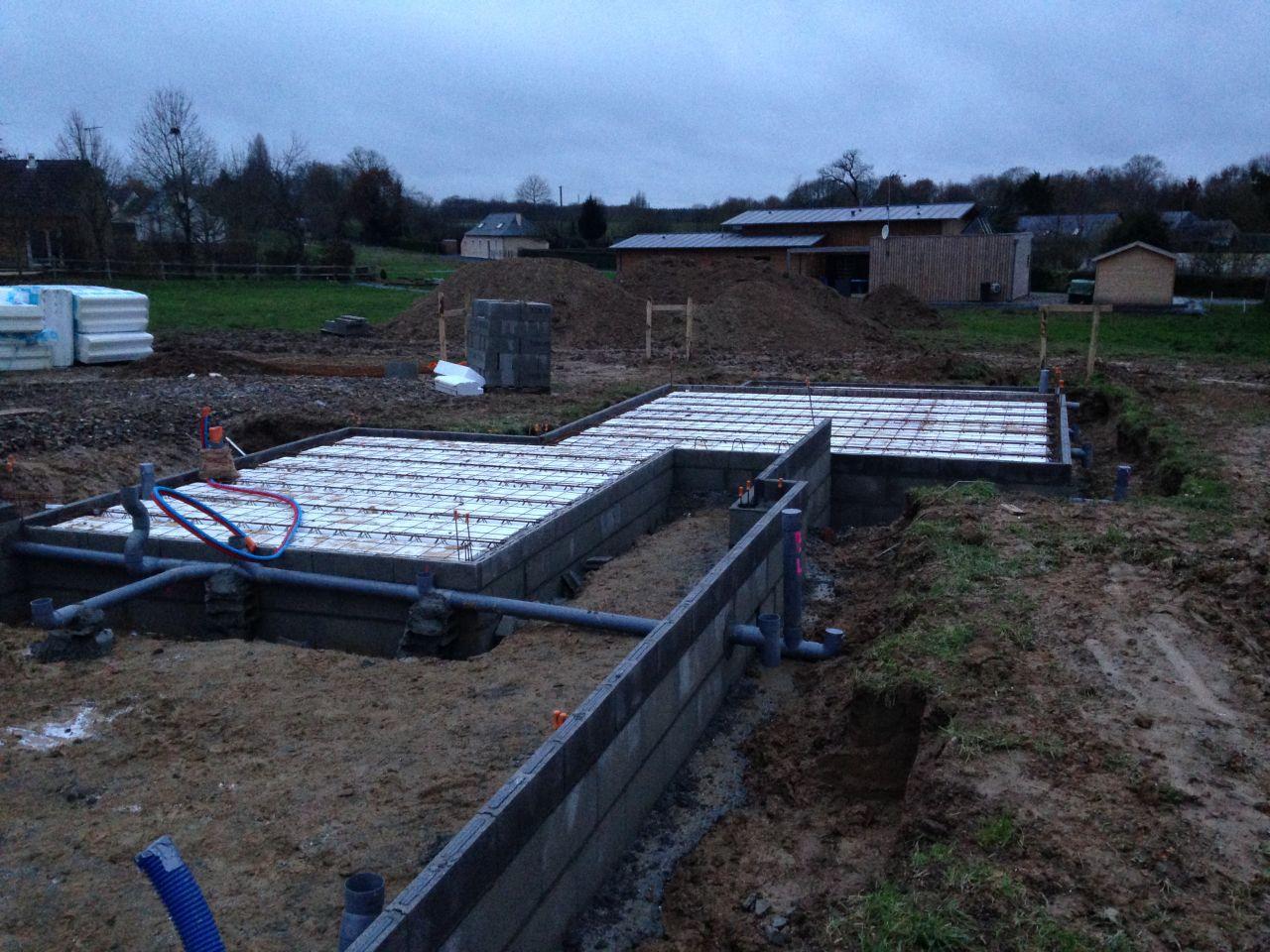 Mise en place de l'isolant au sol et des évacuations d'eaux pluviales et eaux usées