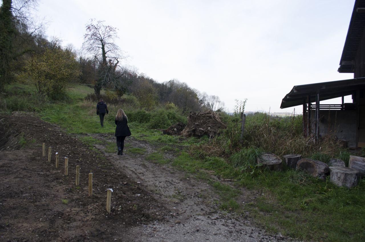 Voici la partie OUEST de la maison. Les petits plots sont la délimitation de notre terrain. Ma copine, de dos, passe sur un chemin agricole (servitude de passage)