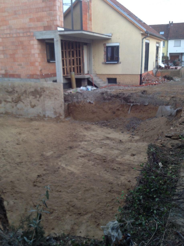 Terrassement terminé au premier plan : des dizaines de bennes de terre évacuées. (la maison en construction sur la photo est toujours celle du voisin...).