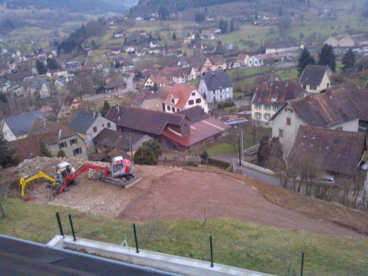 Après 5 jours de travail, le terrain est prêt à accueillir la maison (à gauche). Le concassé 0/60 a été posé sur le chemin d'accès ainsi que sur le parking.