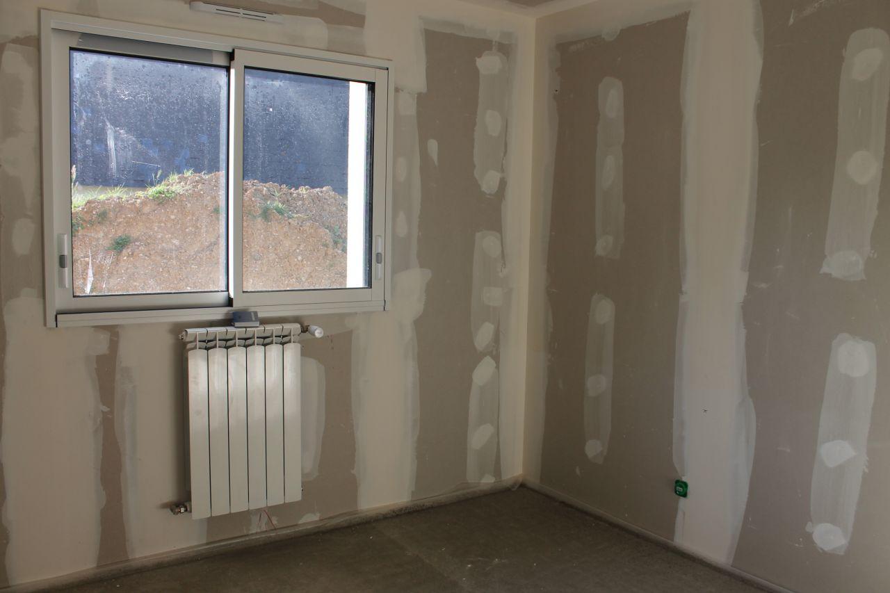 les radiateurs sont posés, les fenêtres sot coulissantes en alu bi-colore: blanc à l'intérieur, gris foncé dehors.