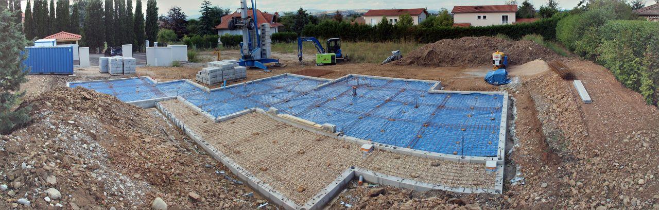 Préparation du plancher bas (sur terre plein) : gravier tout-venant, écran d'étanchéité (sur zone habitable) et ferraillage