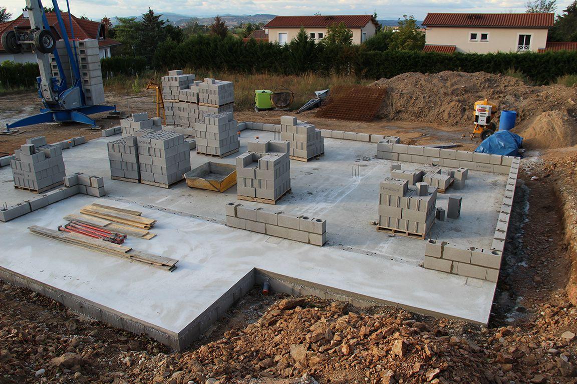 Après la dalle, début de l'élévation des murs du RdC : pose des parpaings