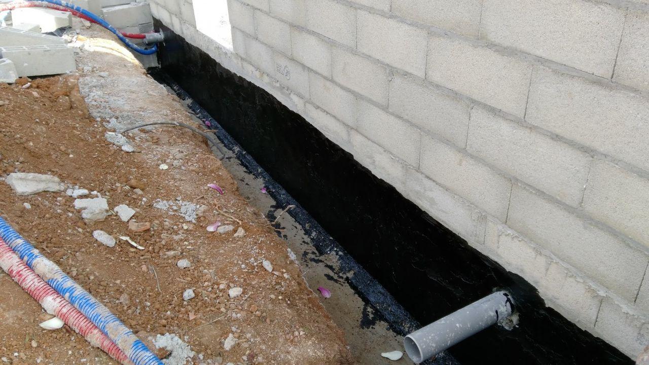 Préparation du drainage entre la maison et le garage : application du goudron