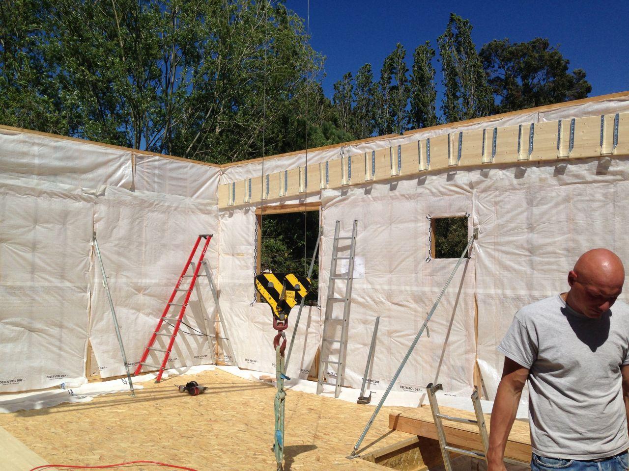 Montage murs du 1er étage. Le revêtement blanc est le pare vapeur. Les poutres qui supporteront le toit sont posées.
