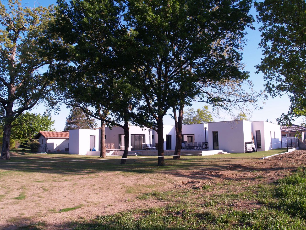 la façade sud et le jardin, vus de l'extrémité sud-est du terrain. L'herbe point et la clôture avance doucement - panneaux rigides sur piquets et demi-chaperons au sol