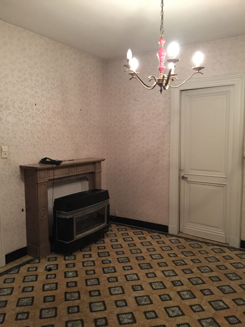 """Pièce de """"repos"""" à côté d'une petite cuisine, d'un couloir et de toilettes.  <br /> Tous les murs vont être abattus pour faire une seule et grande cuisine. <br /> La porte (entrée de la cave) va être déplacée dans le garage."""