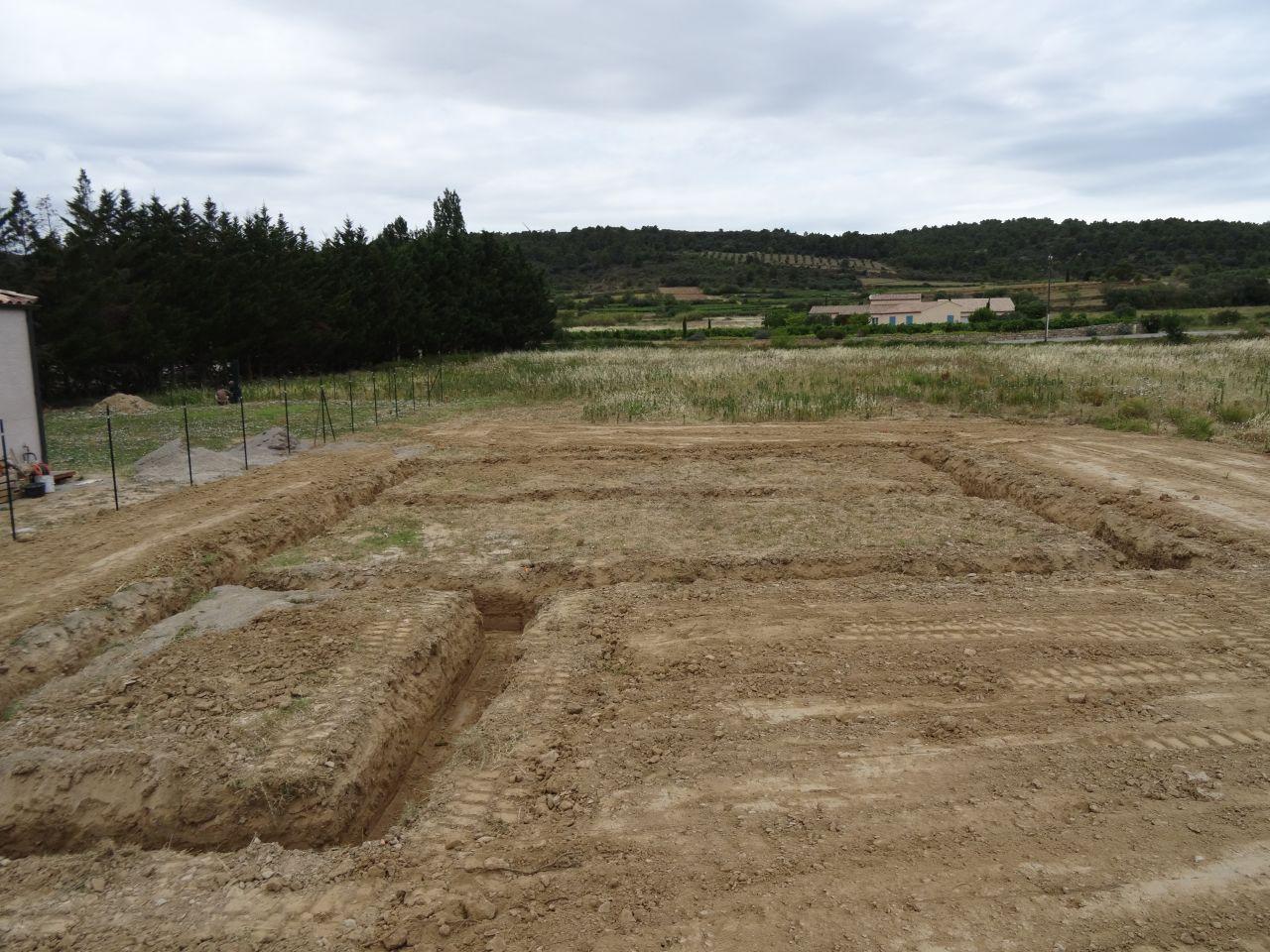 Terrassement du terrain. Creusage des rigoles de fondation et étalage sur la périphérie des terres de fouille.