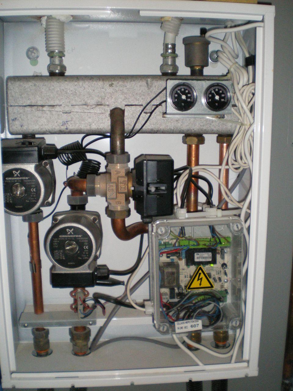 Le répartiteur avec en gris clair en haut, le réservoir de répartition dont les soudures ont lâchées, au centre la vanne 3 voies, qui s'est grippée, en bas à droite, le boitier de commande avec les deux câbles blancs des thermostats d'ambiance.