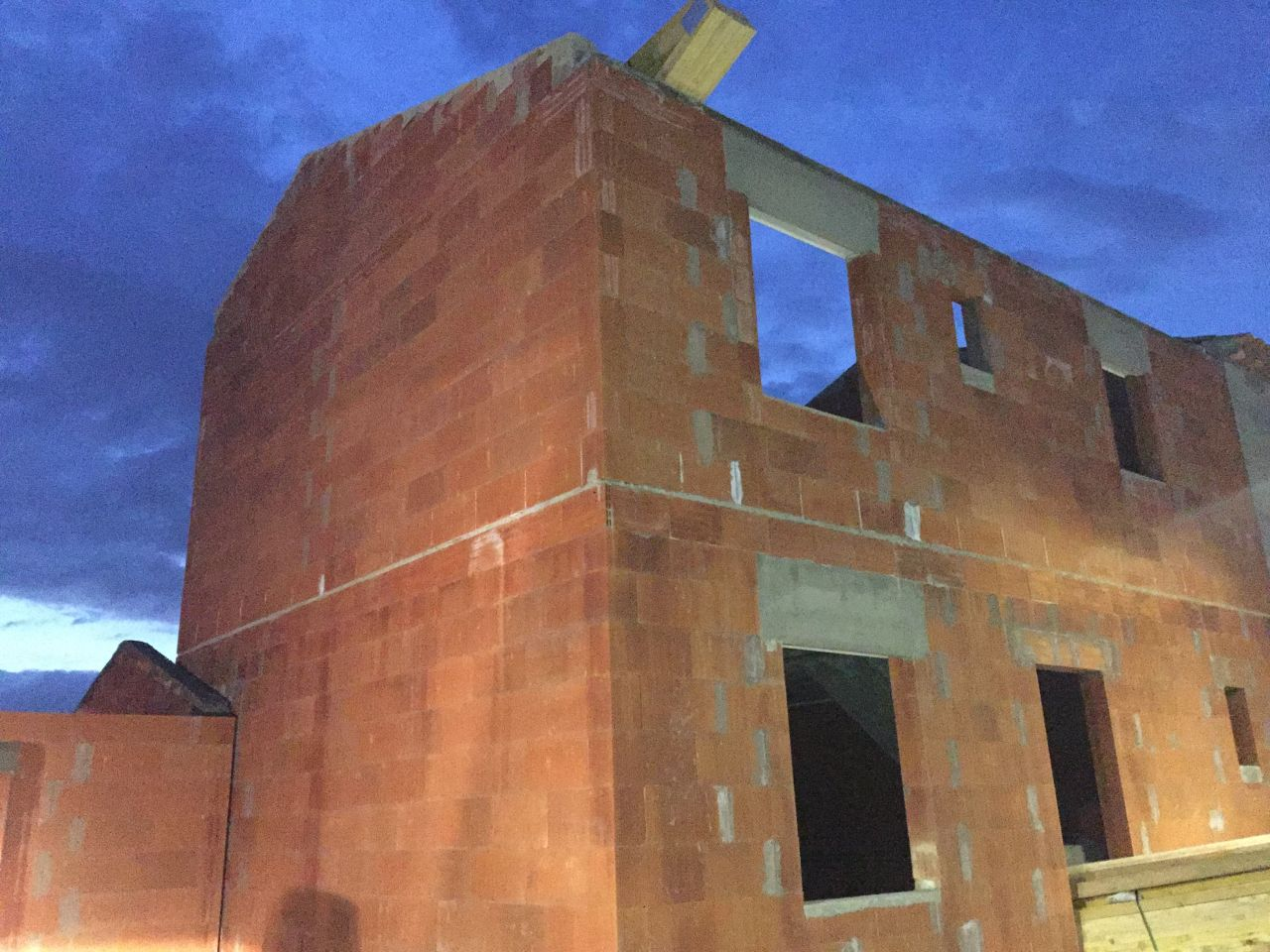 Élévation des murs du garage de la maison terminée, reste à poser la charpente, elle a été livrée ; une partie en bas, une partie posée en haut qu'on peut ...