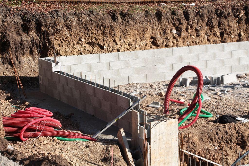 Fondation empierrement garage : Le niveau final apparait avec la 3ème rangée d'agglos. La 4ème rangée s'arrête : début de la future porte de garage