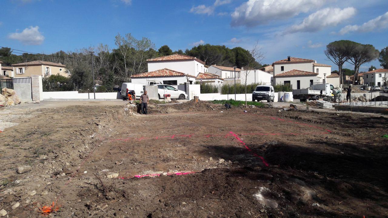 Traçage des lignes de la future maison pour creuser les tranchées à la bombe rose par notre chef de chantier