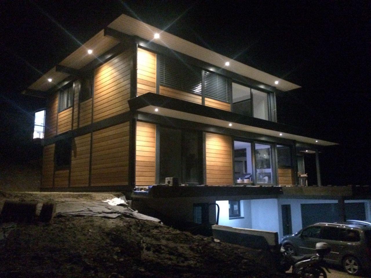 Éclairage des spots extérieur disposés de sorte à éclairer le plus possible de bardage pour mette en valeur la maison.