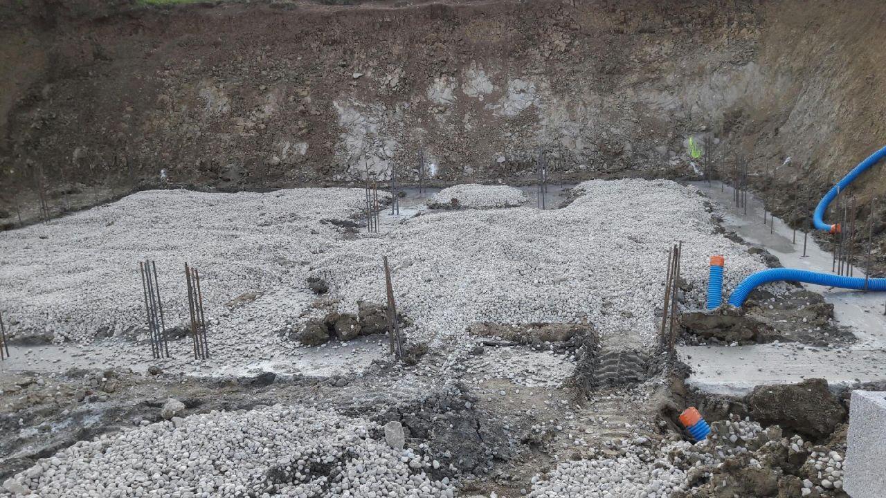 Les fondations coulées et la couche de graviers en place. <br /> On voit les fourreaux en attente pour l'électricité, le téléphone et l'eau. <br /> Les réseaux d'eaux usées ne sont pas encore posés.