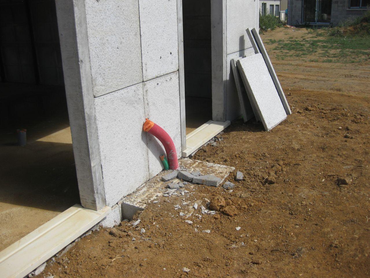 le socle de la pompe a chaleur entre la baie vitrée et la porte de service du garage