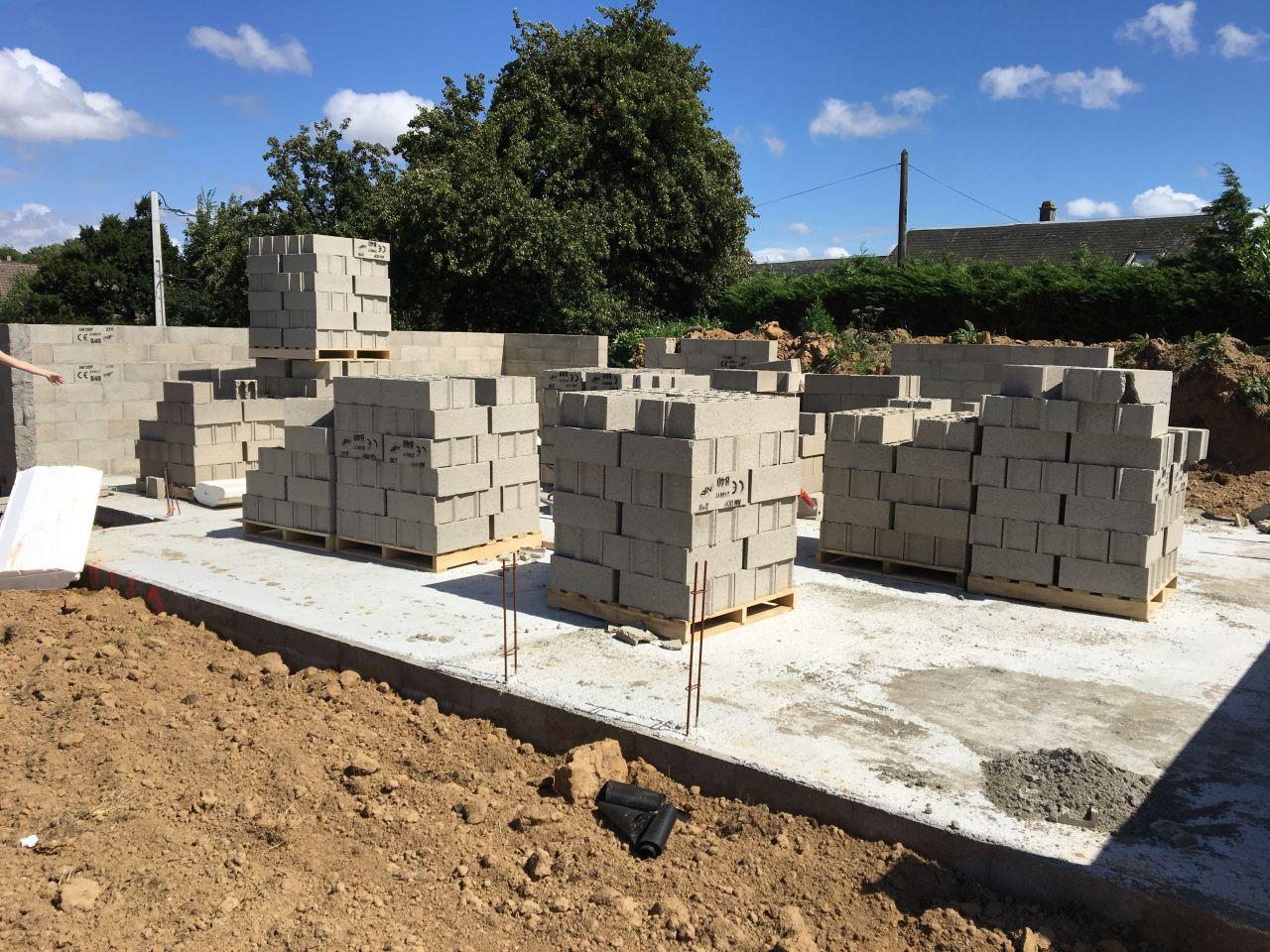Après séchage de la dalle, parpaings déposées pour l'élévation des murs du rez-de-chaussée.