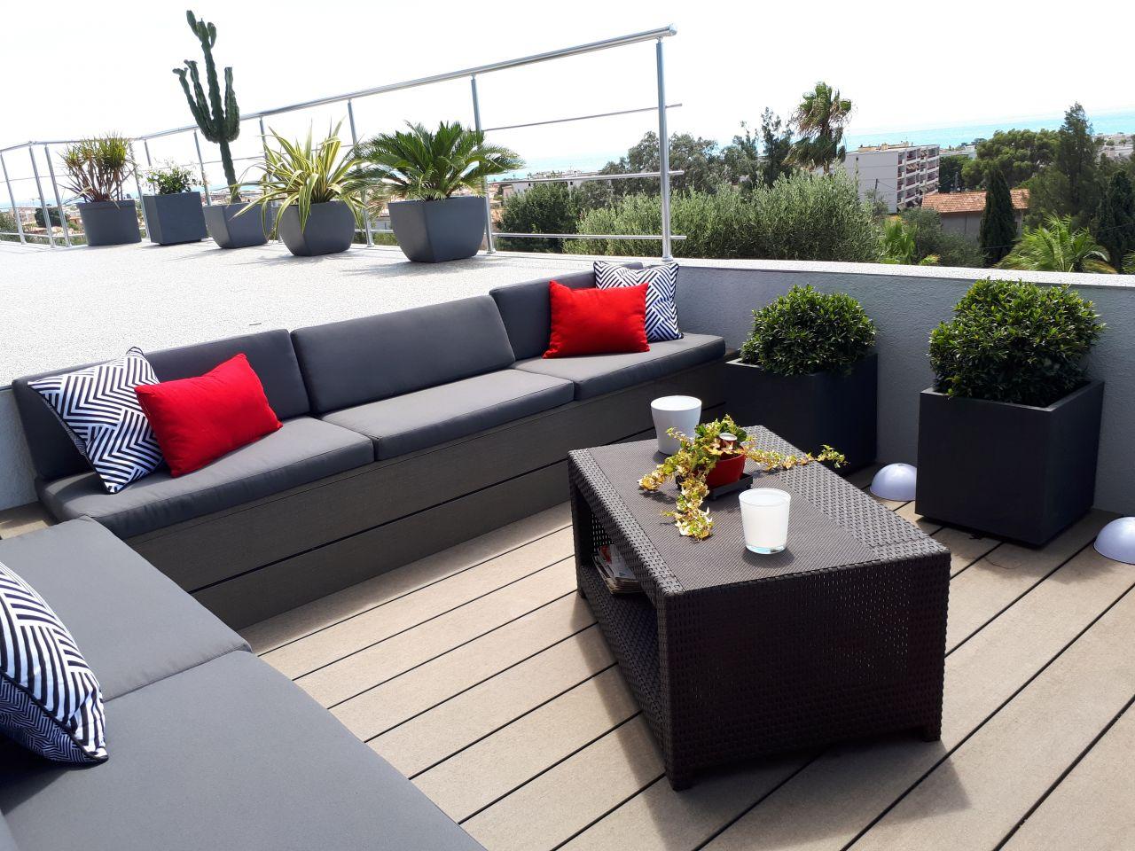 Terrasse encastrée terminée avec les coussins fait sur mesure et les plantes
