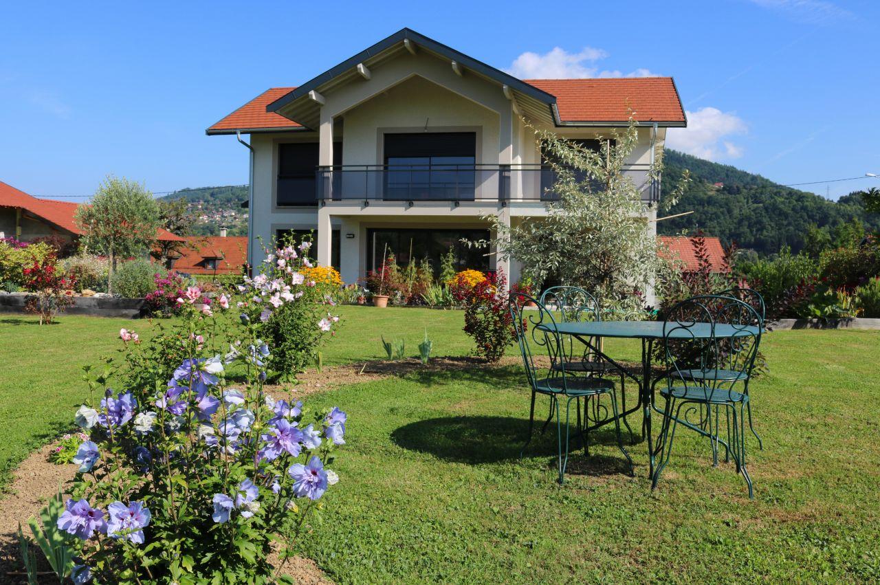 Début septembre au jardin : herbe verte, hibiscus fleuris, nouvelle table et maison sage