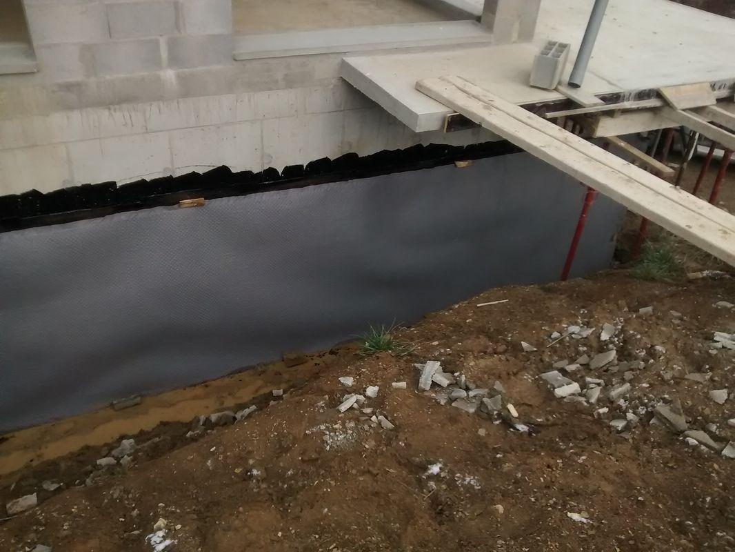 Tada! <br /> Première passe d'étanchéité des murs enterrés faite. <br /> Au terrassier d'intervenir ensuite: première couche de remblai et drainage. <br /> ensuite l'étancheur complétera son ouvrage jusqu'au dessus du niveau du terrain fini projeté (sous les appuis de porte-fenêtres en haut de la photo)