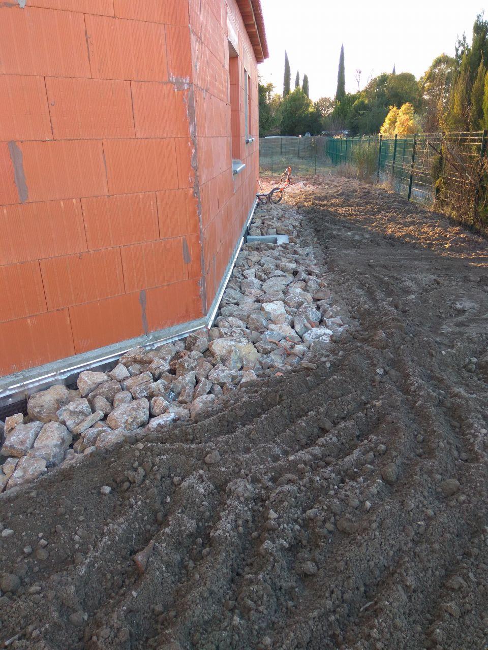Tout le tour de la maison est empierré pour faciliter l?infiltration des eaux de pluie tombées du toit (génoises sans gouttières)vers le drain.