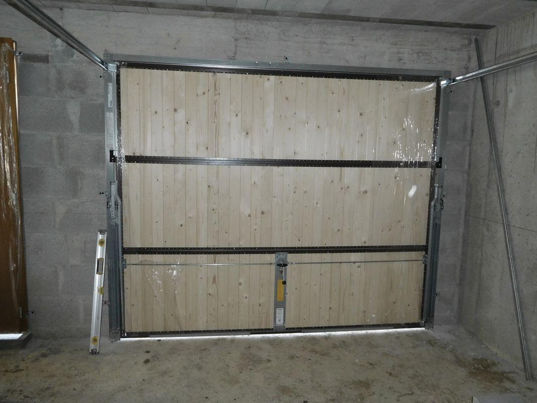 La porte de garage basculante habillée bois rend plutôt bien. On sent qu'elle est lourde mais les ressorts font bien leur boulot et elle se manipule assez facilement. <br /> Vue intérieure.