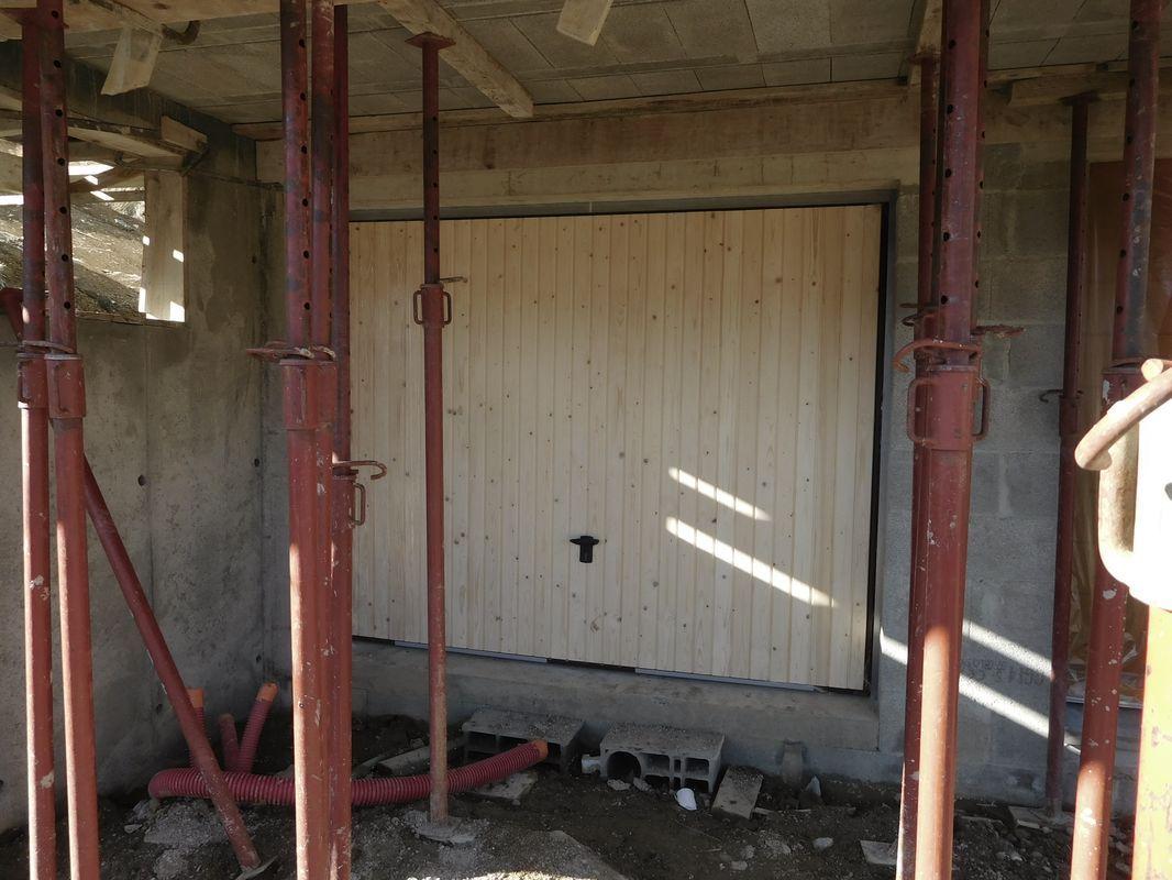 La porte de garage basculante habillée bois rend plutôt bien. On sent qu'elle est lourde mais les ressorts font bien leur boulot et elle se manipule assez facilement. <br /> Vue extérieure.