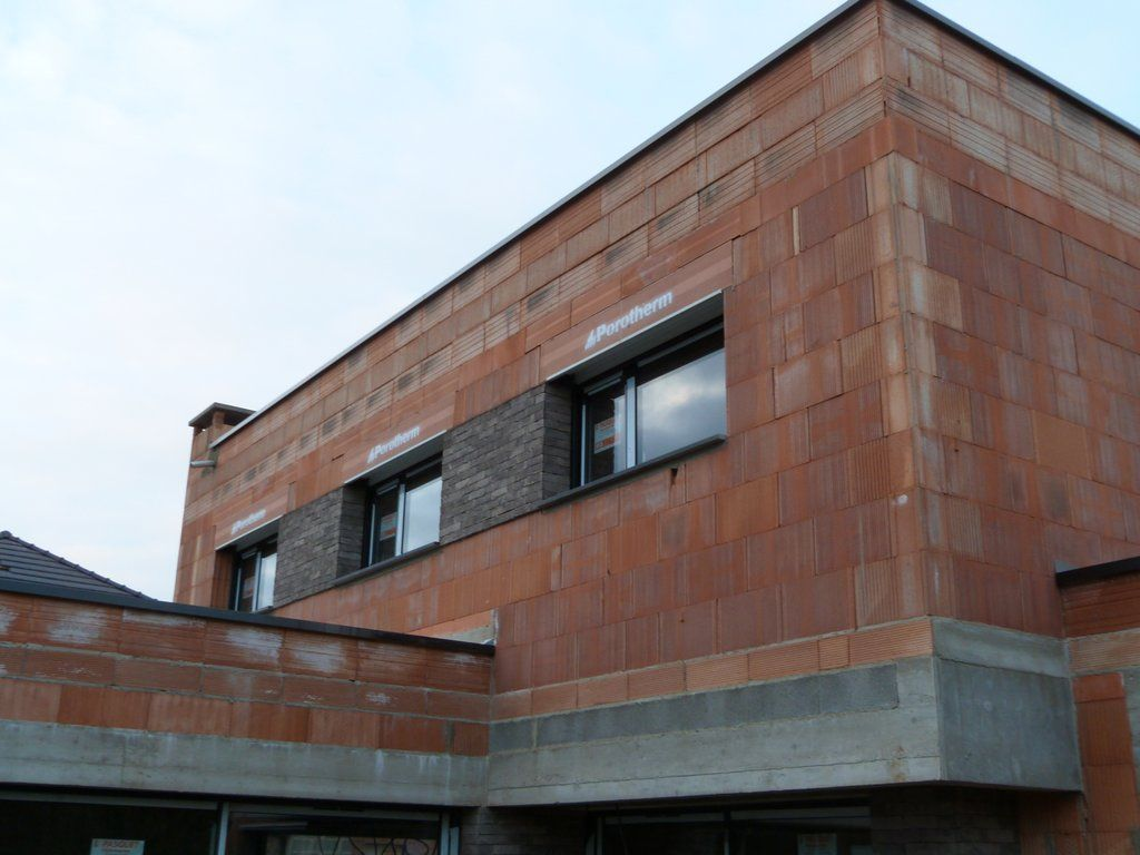 Pose des briquettes entre les fenêtres de l'étage et cheminée terminée