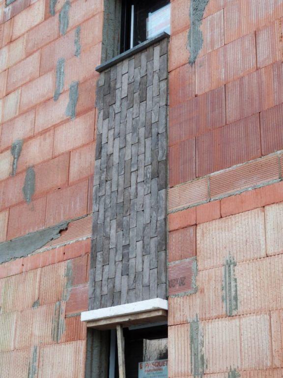 Pose des briquettes entre les fenêtres de la façade