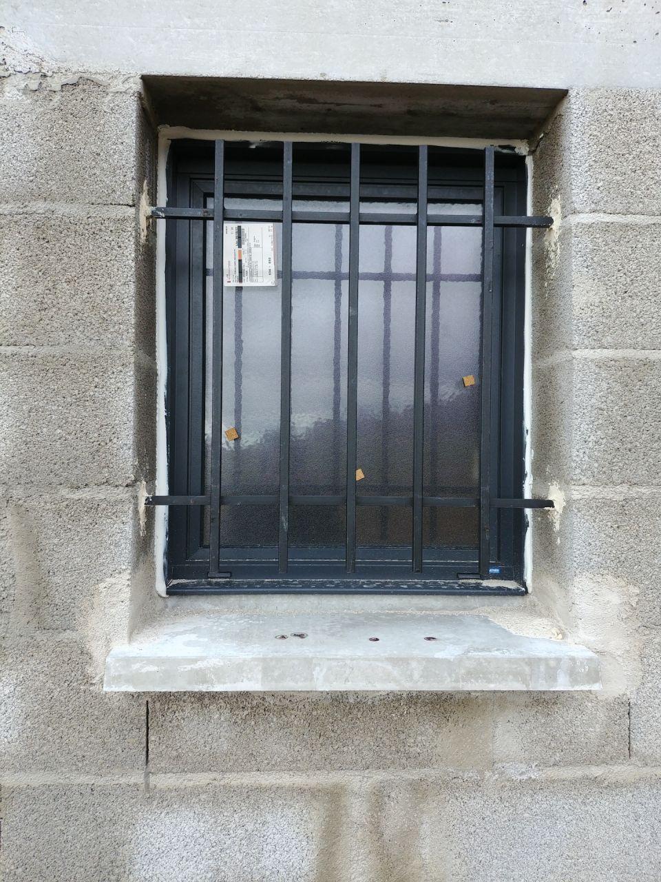 fenêtre ALU avec barreaux. <br /> Le joint silicone me paraît bien épais voire dégueulasse mais je suis sans doute trop méticuleux