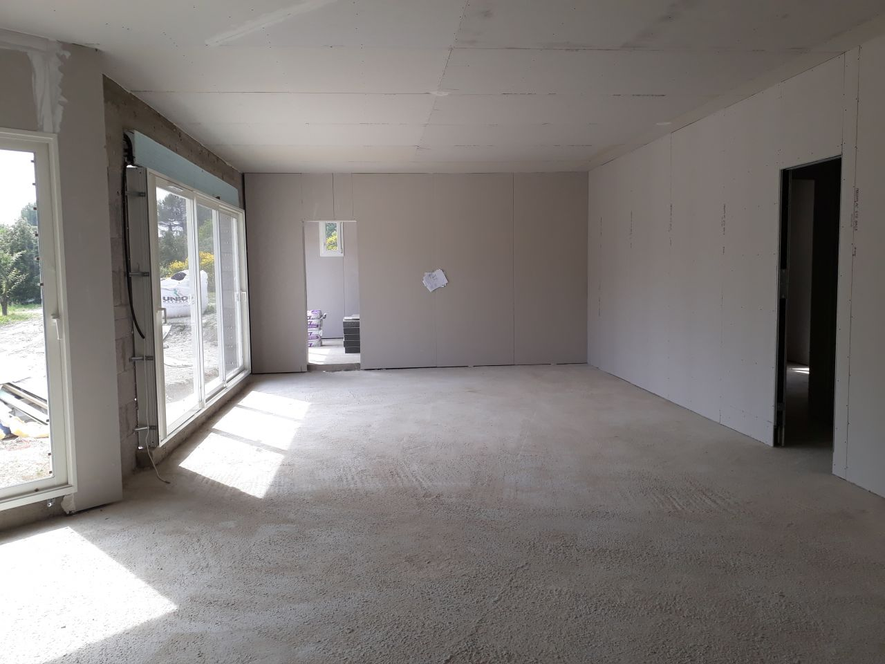 vue de la pièce à vivre, isolation des murs extérieur non terminée autour de la baie. Car lors de la livraison le rail a été endommagé.