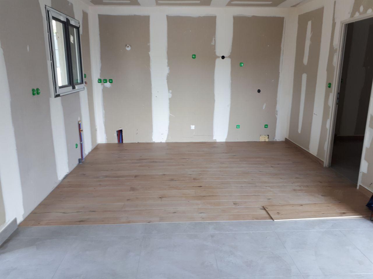 Carrelage imitation bois dans la cuisine et effet béton gris dans la pièce de vie