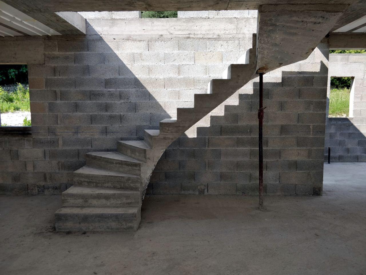 Escalier en béton construit. Une rambarde en fer est prévue.