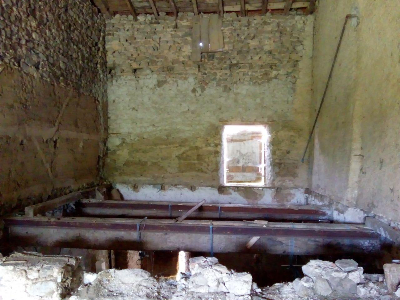 Future chambre du rez-de-chaussée et salle de bains, plancher en cours de retrait. On aperçoit encore des poutres.