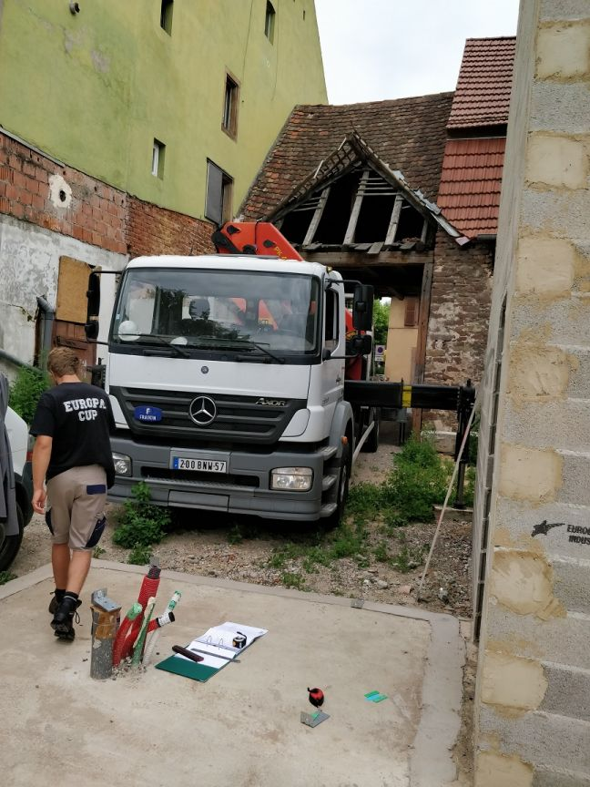 Configuration du terrain pour le montage : le petit camion grue de Heim va chercher quelques panneaux sur le camion et les ramène en passant (tout juste) sous le porche pour les décharger