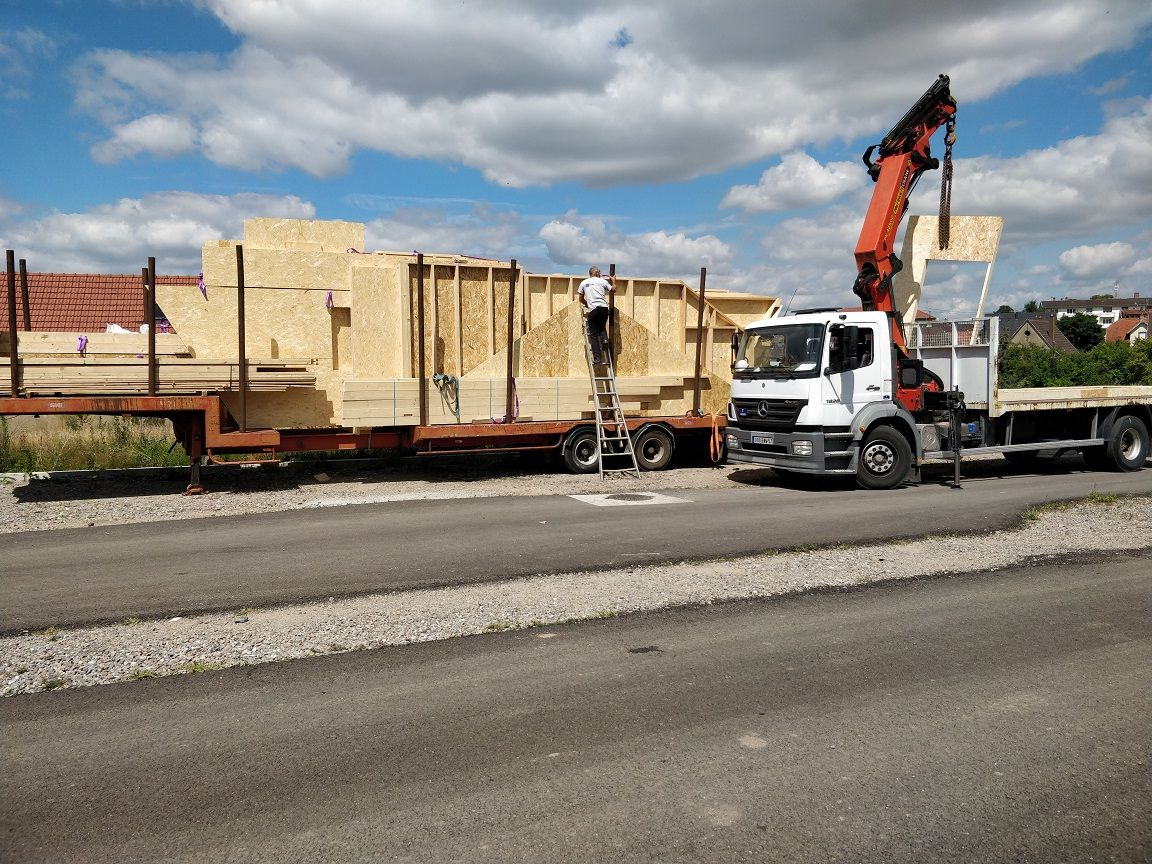 Transfert des panneaux depuis le semi-remorque sur le petit camion grue