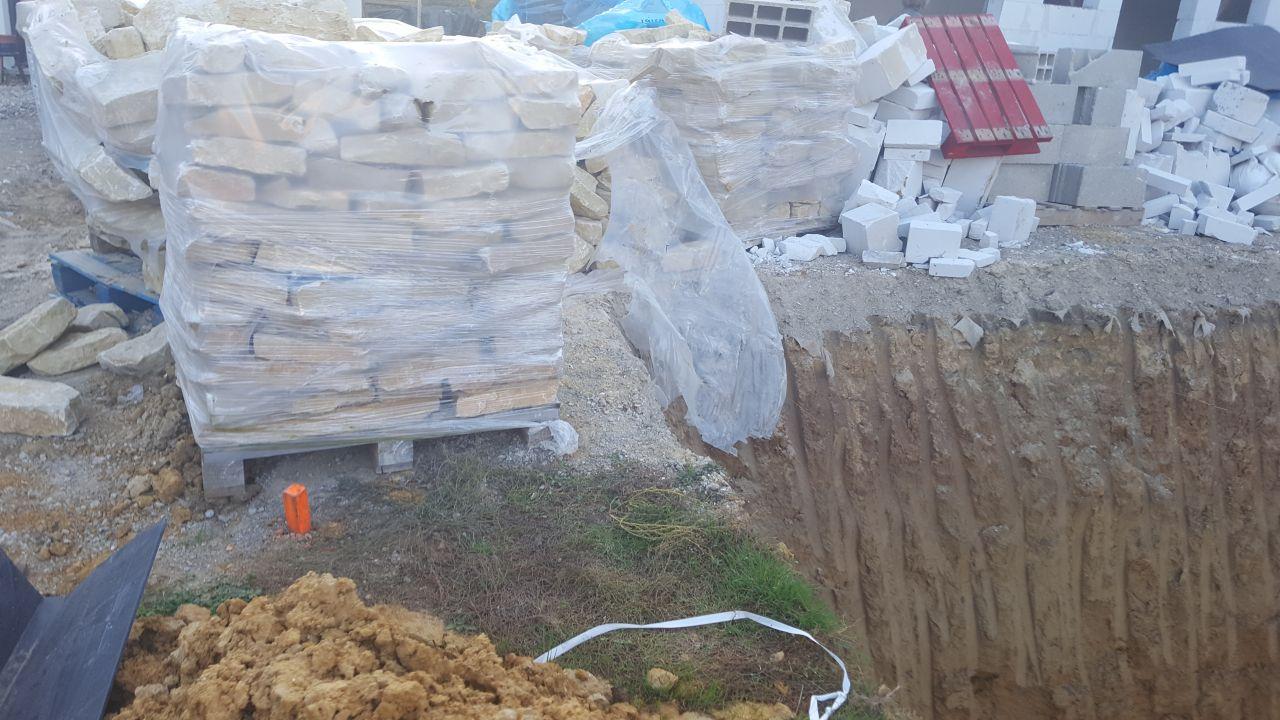 Les palettes (2 tonnes l'une environ) ont été repositionnées très près du bord du trou des voisins (à l'arrêt à ce moment là car ils avaient creusé trop profond et sont tombés sur la nappe phréatique a priori).