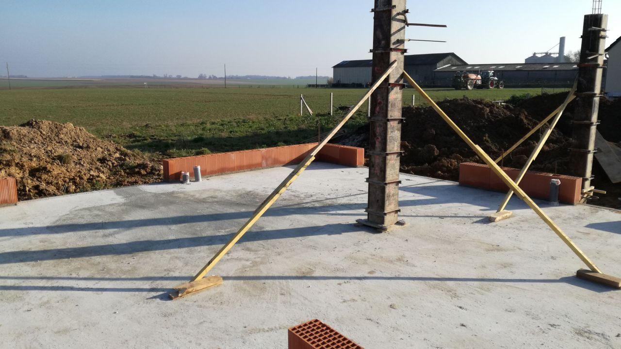 Montage du premier rang de briques pendant le séchage de la chape et coulage des poteaux