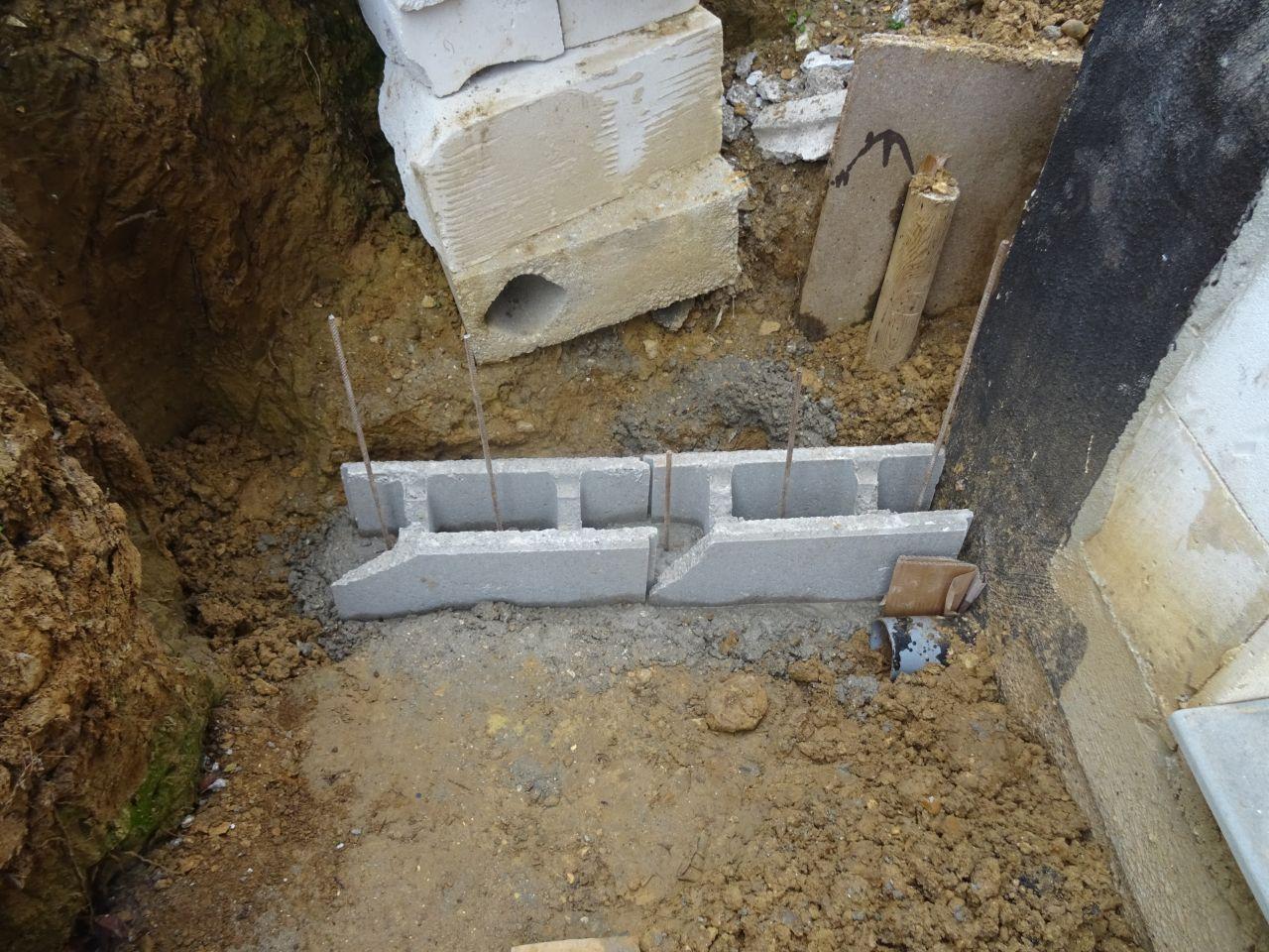 Un futur mur de soutènement. Les briques (de récup) ont été posées sur le ciment tout frais. Les ferraillages sont certainement juste des tiges droite plantées dedans (je ne sais pas si c'est conforme).