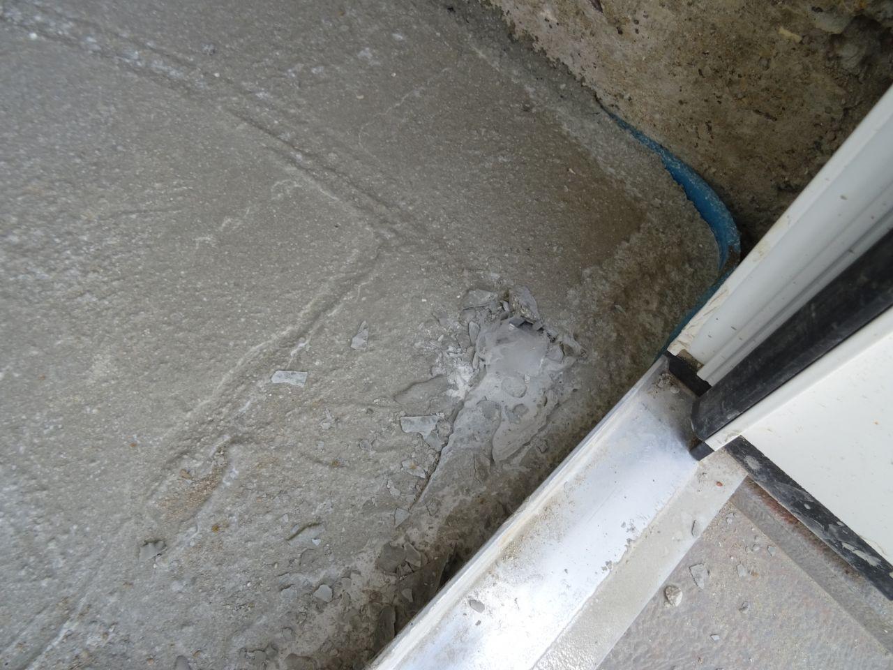 Un morceau de plastique pris dans la dalle. <br /> Malin d'avoir laissé le plastique sur la porte au moment du coulage de la dalle...