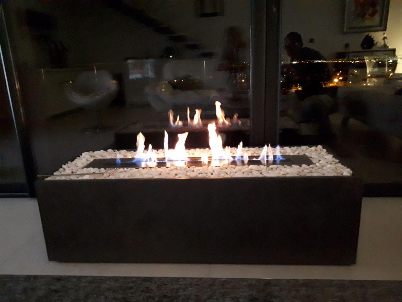 Nous avions envie d'une cheminée à éthanol que nous puissions déplacée. on a acheté le foyer et on a fait les plan, à la dimension souhaitée et on l'a mise sur roulettes (les roulettes sont cachées) on la p^recouverte d(un enduit façon béton métallisé et on a mis des gales blancs autour du foyer (qui repose sur une armature métallique) voilà le rendu!