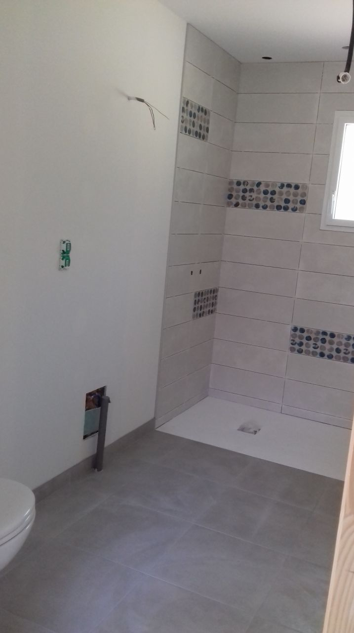salle de bain principale: carrelage, faïence et receveur douche posés.
