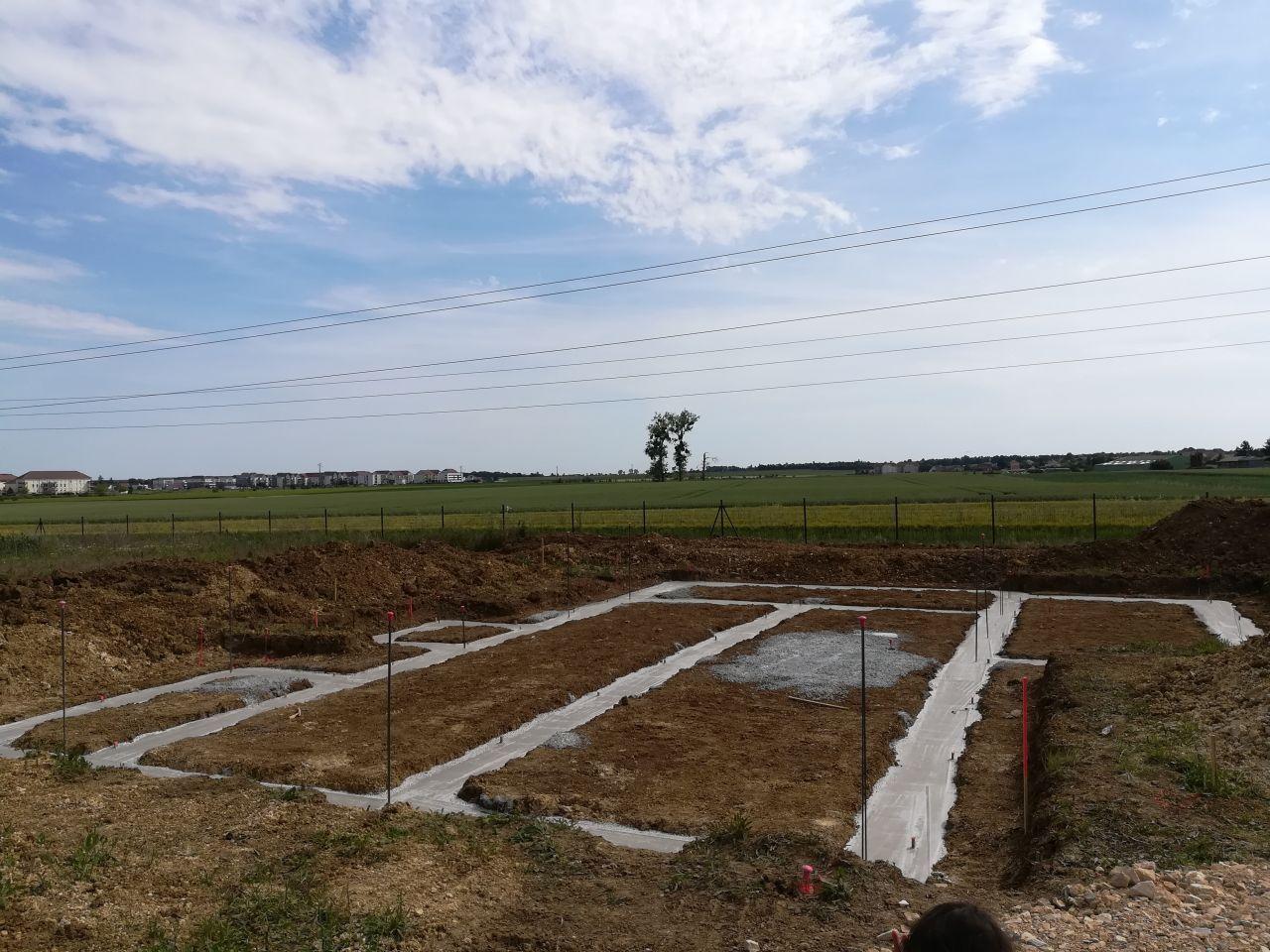 Vue depuis l'entrée du terrain sur les travaux de terrassement et de fondations réalisés