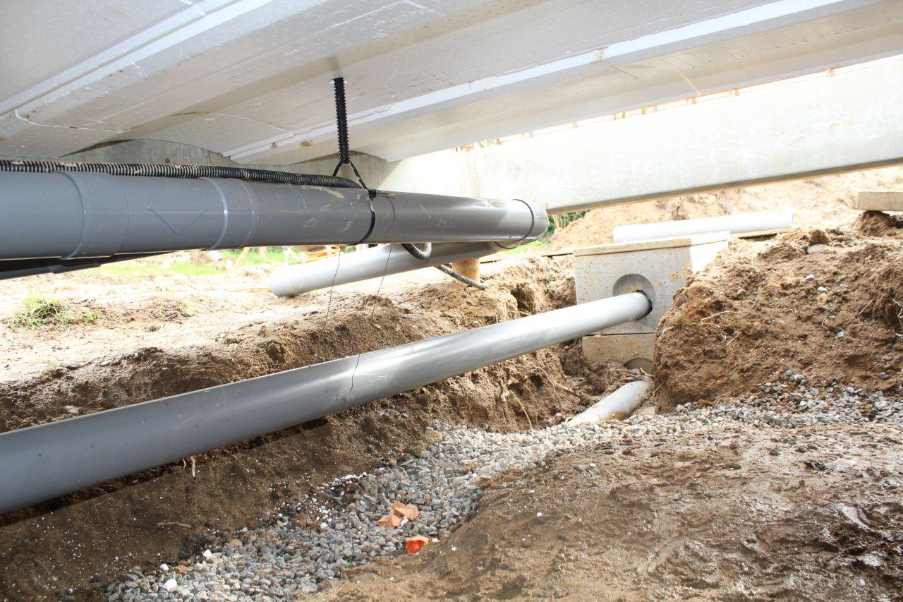 Réseaux sous dalle : Assainissement tuyau PVC du haut vers station de relevage à poser, au milieu : trop plein de la citerne souple de récupération d'eau de pluie vers regard EP, en bas : drain agricole sous gravier vers regard EP