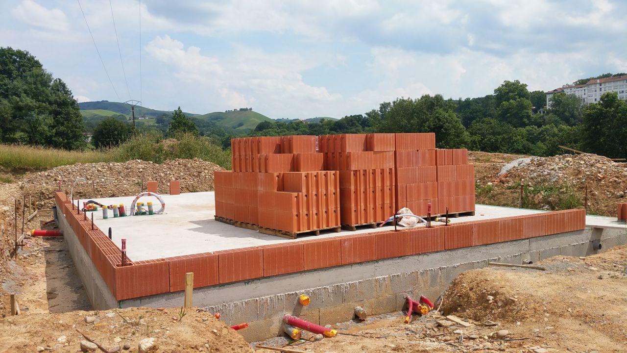 Début du montage des murs en briques.