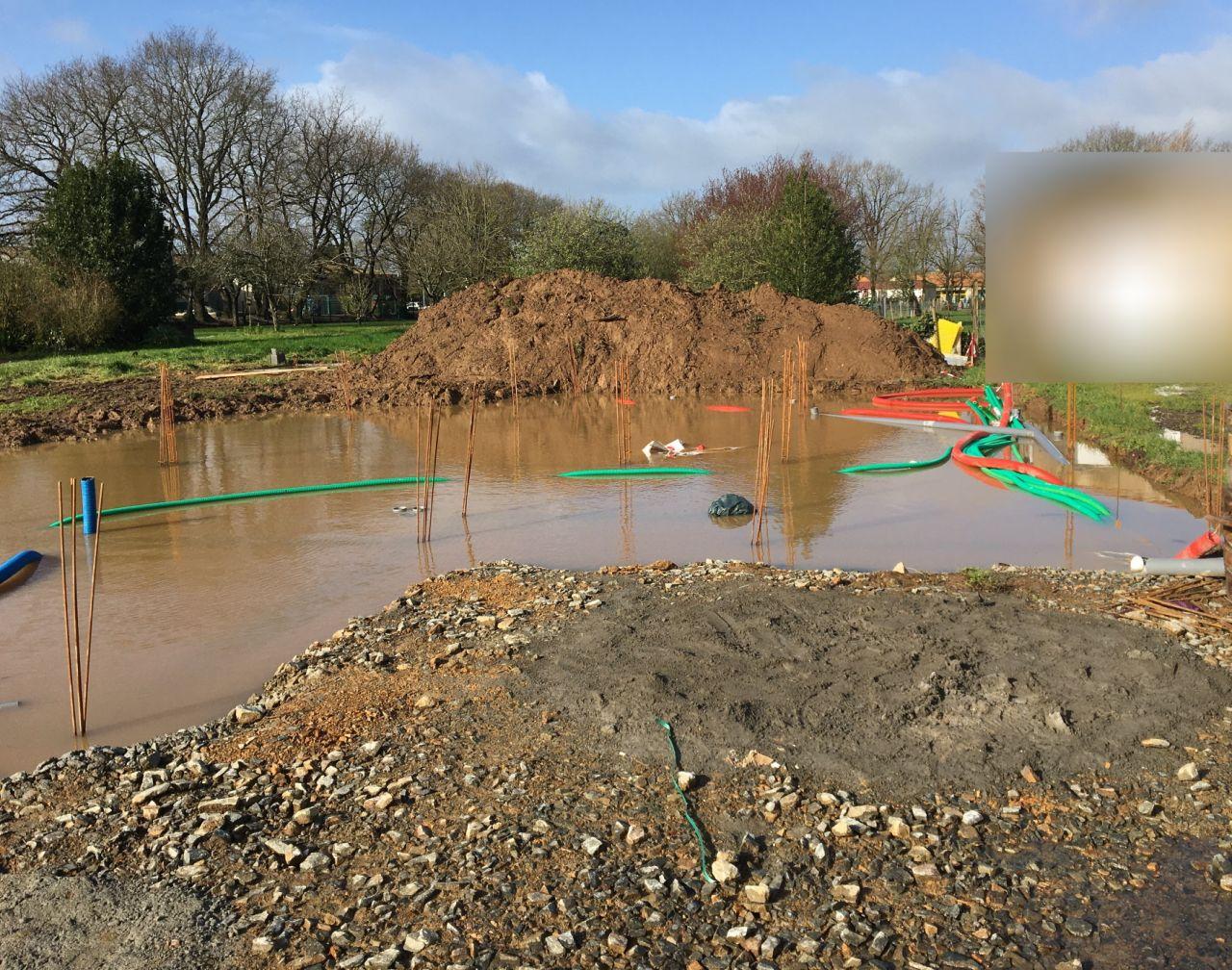 7 jours après la réalisation du soubassement, la construction est totalement sous l'eau, les tuyaux flottent.